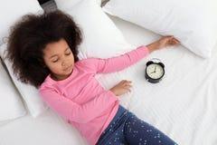Piccola ragazza afroamericana sveglia con la sveglia che dorme a letto fotografie stock libere da diritti