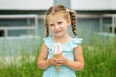 Piccola ragazza allegra con il gelato sulla via Il concetto dell'infanzia, stile di vita, alimento, estate Fotografia Stock