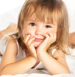 Piccola ragazza allegra sorridente felice a letto isolata Immagine Stock
