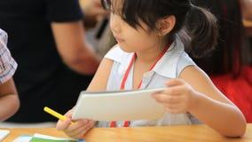 Piccola ragazza asiatica che disegna un'immagine sulla tavola stock footage