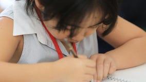 Piccola ragazza asiatica che disegna un'immagine sulla tavola video d archivio