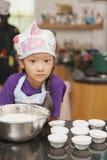 Piccola ragazza asiatica che fa ovatta agglutinare Immagini Stock