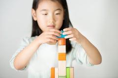 Piccola ragazza asiatica che gioca i blocchi di legno variopinti Immagine Stock