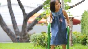 Piccola ragazza asiatica che guida velocemente Carting/carretto di spinta al campo da giuoco/parco video d archivio