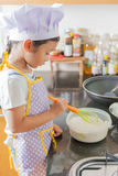Piccola ragazza asiatica che produce pancake Fotografie Stock Libere da Diritti