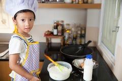 Piccola ragazza asiatica che produce pancake Immagine Stock