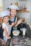 Piccola ragazza asiatica che produce pancake Immagini Stock