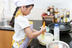Piccola ragazza asiatica che produce pancake Fotografie Stock