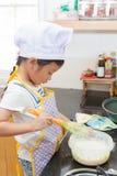 Piccola ragazza asiatica che produce pancake Immagini Stock Libere da Diritti