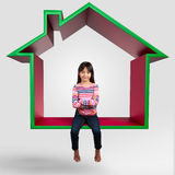 Piccola ragazza asiatica che si siede sulla casa virtuale 3D Immagini Stock