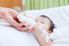Piccola ragazza asiatica che si trova su un letto medico Immagine Stock Libera da Diritti