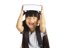 Piccola ragazza asiatica che tiene i libri con il suo zaino Immagini Stock