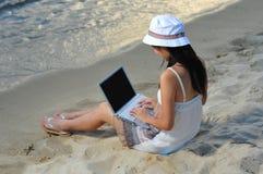 Piccola ragazza asiatica cinese sulla spiaggia con il computer portatile Fotografia Stock