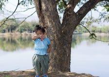 Piccola ragazza asiatica con l'albero vicino alla laguna Immagini Stock