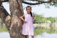 Piccola ragazza asiatica con l'albero vicino alla laguna Fotografia Stock