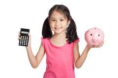 Piccola ragazza asiatica con un calcolatore e un porcellino salvadanaio Immagine Stock Libera da Diritti