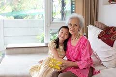 Piccola ragazza asiatica e celebrazione senior della donna a casa insieme fotografia stock