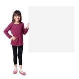 Piccola ragazza asiatica sorridente che sta con il foglio bianco di grande carta Immagine Stock