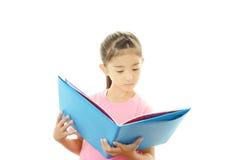 Piccola ragazza asiatica sveglia che legge un libro Fotografia Stock