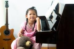 Piccola ragazza asiatica sveglia in cinese besi di seduta del vestito dal cinese tradizionale immagine stock