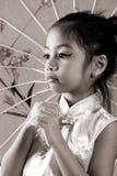 Piccola ragazza asiatica sveglia nella seppia immagine stock