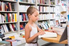 Piccola ragazza astuta che legge un libro nella biblioteca di scuola Immagini Stock Libere da Diritti