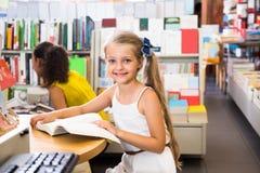 Piccola ragazza astuta che legge un libro nella biblioteca di scuola Fotografia Stock