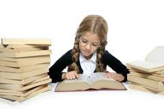 Piccola ragazza bionda del banco dell'allievo che legge vecchio libro Immagini Stock Libere da Diritti