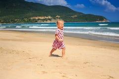 Piccola ragazza bionda nei funzionamenti chiazzati del vestito dalla spuma di Wave lungo la spiaggia Immagini Stock