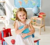 Piccola ragazza bionda sorridente che tiene libro blu nella classe di scuola Fotografia Stock