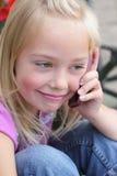 Piccola ragazza bionda su un cellulare Fotografia Stock Libera da Diritti