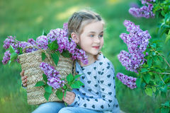 Piccola ragazza bionda sveglia sorridente del bambino 4-9 anni con un mazzo del lillà nelle mani in jeans e camicia Fotografia Stock