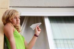 Piccola ragazza caucasica bionda con l'aereo di carta in finestra Fotografie Stock