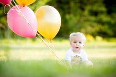 Piccola ragazza caucasica bionda felice fuori con i palloni fotografia stock