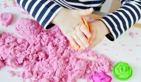 Piccola ragazza caucasica che gioca con la sabbia cinetica rosa a casa immagini stock