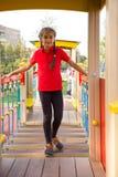 Piccola ragazza caucasica che gioca sul campo da giuoco, camminante sui punti d'oscillazione e provante al keeep il suo equilibri fotografia stock