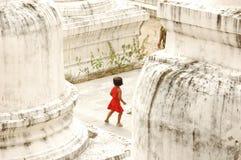 Piccola ragazza che gioca pellame - e - ricerca al tempiale buddista Fotografia Stock