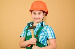 piccola ragazza che ripara con il martello in officina Sviluppo di puericultura Professione futura Architetto dell'ingegnere del  immagine stock
