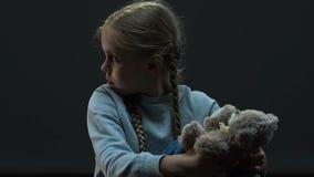 Piccola ragazza che si siede nell'oscurità che gioca con l'orso del giocattolo, abuso della famiglia, maltrattamento archivi video