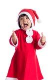 Piccola ragazza cinese asiatica felice del Babbo Natale con i pollici su Fotografia Stock