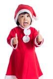 Piccola ragazza cinese asiatica felice del Babbo Natale con i pollici su Immagini Stock