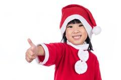 Piccola ragazza cinese asiatica felice del Babbo Natale con i pollici su Fotografia Stock Libera da Diritti