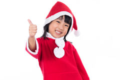 Piccola ragazza cinese asiatica felice del Babbo Natale con i pollici su Fotografie Stock