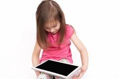 Piccola ragazza con il computer della compressa su fondo bianco Immagine Stock