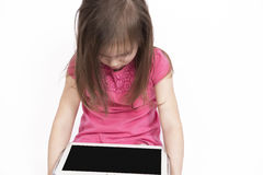 Piccola ragazza con il computer della compressa su fondo bianco Immagini Stock Libere da Diritti
