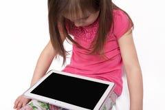 Piccola ragazza con il computer della compressa su fondo bianco Fotografia Stock