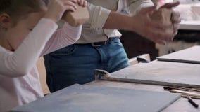 Piccola ragazza del bambino con il padre adulto che fa gli oggetti delle terraglie dentro stock footage