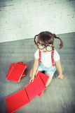 Piccola ragazza del nerd con i vetri ed i libri Fotografia Stock