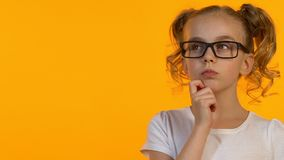 Piccola ragazza del nerd in occhiali che pensa alla decisione di compito o alla carriera futura stock footage