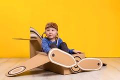 Piccola ragazza del sognatore che gioca con un aeroplano del cartone Infanzia Fantasia, immaginazione Fotografia Stock